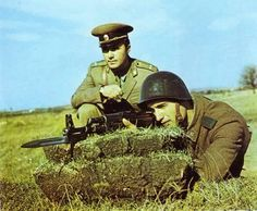 A Bulgarian People`s Army lieutenant observing his new recruit's target shooting abilities.