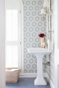 Light and airy bathroom with patterned wallpaper and penny tile floor.