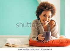 Beautiful young African woman enjoying a cup of coffee while relaxing at home.
