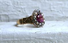 A purple sapphire ring set with seed pearls is fit for a queen.
