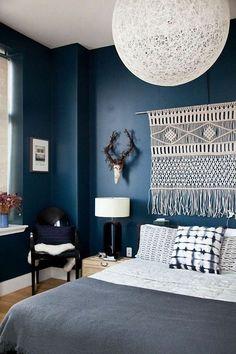 Un mur bleu pétrole décoré d'une suspension en tissage en tête de lit qui rappel le choix raffiné du linge de lit