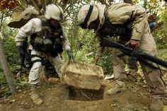 AD DAWR, IRAQ - DECEMBER 15: American soldiers remove a Styrofoam cover that plugged up the spider hole where Saddam Hussein hiding when he was captured December 15, 2003 in Ad Dawr, Iraq. Iraqs notorious dictator was captured in a raid at the compound on December 13.