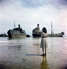 A woman on Omaha Beach looks out at ruined ships used in the D-Day storming of Normandy, France. Photograph by David Seymour, 1947