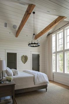 Cottage bedroom with gray shiplap vaulted ceiling features two oak wood beams an. Cottage bedroom with gray shiplap vaulted ceiling features two oak wood beams and a small candelabr Vaulted Ceiling Bedroom, Vaulted Ceiling Lighting, Shiplap Ceiling, Wood Ceilings, Ceiling Decor, Ceiling Chandelier, Wood On Ceiling Ideas, Vaulted Ceiling With Beams, Vaulted Ceilings