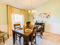 Keep a bright paint color from overwhelming by using it above a chair rail! This dining room has a sunny, spring appeal with a spring green walls and sunny yellow accents. Highland Homes' Remington IV model home in Ocala, Florida.