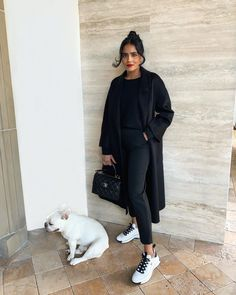All black always looks expensive. Black knit and cropped black pants with Chanel white sneakers and black long coat