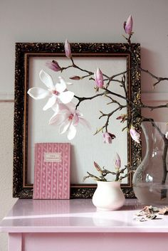 Beautiful Japanese magnolia branches act as the artwork to the over sized vintage frame that's layered against the wall.