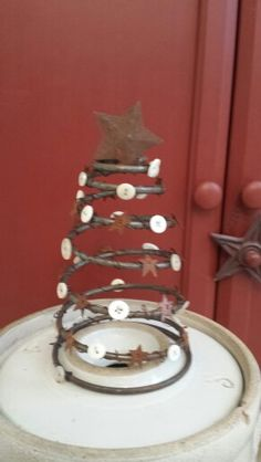 """Primitive bed spring Christmas tree - """"my version has rusty stars and old buttons. I strung the buttons on using very fine wire."""""""