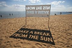 """Take a Break From The Sun"". As can be seen in the image above, the message is created by reversed type that casts a shadow on the sand. """