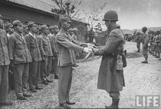 American officer accepting sword of Japanese officer during the surrender of a naval base to American forces following the capitulation of Japan. Location:Onomichi, Honshu, Japan Date taken: September 1945 Photographer:Carl Mydans © Time Inc.