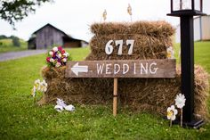 Rustic wedding sign + welcome area idea - hay bales, wood sign + fresh flowers {Jasmine Rose Photography}