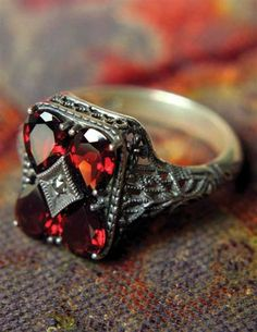 Once an Edwardian engagement ring, this gorgeous art deco design is rendered in precious garnet.