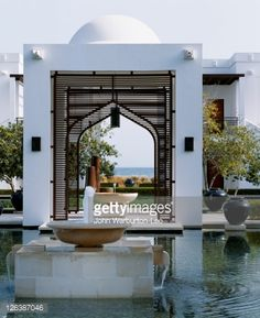 Stock Photo : Oman, Muscat. Contemporary architecture with an Omani theme blends crisp white lines, arches and domes at the water garden at the Chedi Hotel