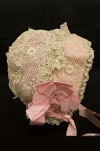 Child's Irish crochet bonnet, ciirca 1910. Each side is decorated with a pink ribbon rosette.
