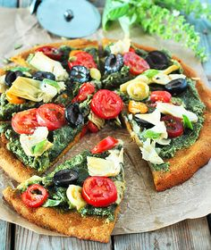 This is my Mediterranean Pumpkin Pizza, it captures the flavors of the Mediterranean plus Fall. Lots of fresh, juicy tomatoes, olives, artichoke hearts, pumpkin seed pesto, basil on top of a pumpkin flavored quinoa crust.