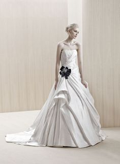 """Ecuador"" strapless satin A-line wedding dress with a draped skirt, lace applique details on the bodice, and a black ribbon detail at the waist, Blue By Enzoani"