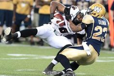 Marcus Henry of the Ottawa RedBlacks is tackled by Desia Dunn of the Winnipeg Blue Bombers at Investors Group Field on Thursday in Winnipeg. Ottawa Redblacks, Winnipeg Blue Bombers, Canadian Football League, Investors, Football Helmets, Thursday, Spaces, Group, Sport