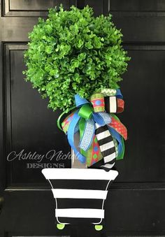 "This amazing Topiary Door Hanger will be a great addition to your home.   Made using ¼"" plywood and artificial eucalyptus greenery, adorned with a bow. There is a wire hanger on the back of the greenery. This piece is also painted black on the back for a more polished look. Height 34"", Width 16"" and Greenery section is 9"" Deep"