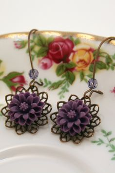 """1008- Antiqued Vintaj Brass Lace Filigree and Flower Cabochon Earrings $16 Description: These earrings are the best for any vintage and girlie soul!! These are beautiful violet colored floral cabochons atop Vintaj Brass lace filigrees. They are suspended by long Vintaj Brass kidney ear wires adorned with round Swarovski crystals in Tanzanite. These earrings measure approximately 1 3/4"""" from top of ear wire."""