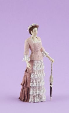 NAME: Evelyn - PERIOD: 1875-1881.  Lady in a walking suit made of printed cotton and lace. Silk hat adorned with flowers. Umbrella included.