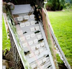 The escort cards were placed on antique white shutters decorated with moss and trailing ribbons. The shutters leaned against one of the large trees outside the reception tent. Each table card had a sepia photograph of a location in South Africa that is sp...