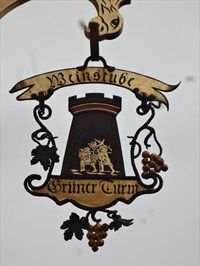 This is a unique artistic shop sign for a restaurant called 'Weinstube Grüner Turm' (Wine bar Green Tower). It is located at the intersection of 'Turmstraße' and 'Untere Gasse' in Böblingen, Germany, Baden-Württenberg.