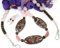 This unique eye-catching statement necklace features stylish gemstones such as rose quartz, ocean jasper, and pink rhodochrosite as well as brown