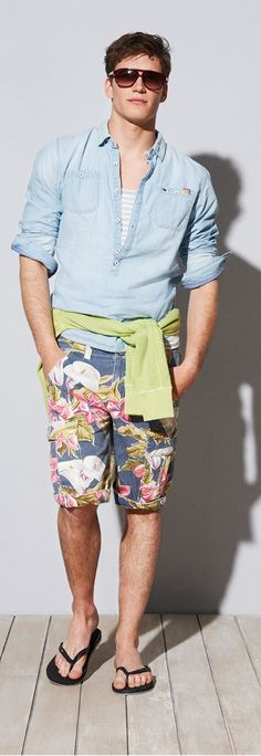 Shop this look on Lookastic:  https://lookastic.com/men/looks/v-neck-sweater-denim-shirt-tank-shorts-flip-flops-sunglasses/11632  — Dark Brown Sunglasses  — Light Blue Denim Shirt  — Grey Horizontal Striped Tank  — Green-Yellow V-neck Sweater  — Navy Floral Shorts  — Black Flip Flops
