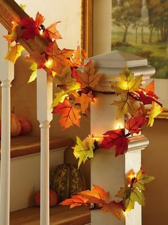 Twinkle light and leaf decorated fall / autumn stair banister
