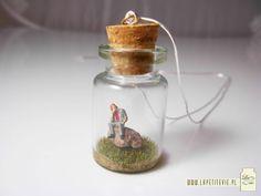 """Tak wygląda wisior w kolekcji """"La petite vie"""" - to mała buteleczka, w której umieszczona została maleńka scenka.   Wisior zawieszony jest na długim, srebrnym łańcuszku.  (This is what a """"La petite vie"""" necklace looks like. It is a bottle with a tiny scene inside suspended from a long, silver snake-chain."""