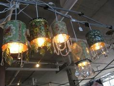 DIY Vintage tea tin pendant lights: Just buy a low-wattage lamp kit, drill a hole the appropriate size in the bottom of the tin, wire it, attach pendants & voila!