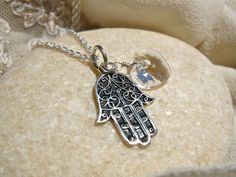 Hand of Fatima necklace ~ silver. This pretty sterling-silver Hamsa Hand of Fatima pendant is accompanied by a birthstone crystal and sterling silver heart. The Hamsa (or Hand of Fatima) is a palm-shaped amulet used in many societies and religions as a sign of protection - providing defense against the 'evil eye' and strengthening the vulnerable or weak.