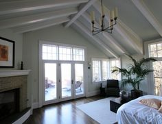 Option 2: paint exposed beams bright white to match current plan to paint door and window moulding bright white (throughout third floor space). Paint walls and vaulted ceilings a soft bluish gray color for clean contrast.