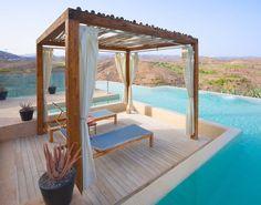 pergola autoportée en bois de design moderne décorée de rideaux blancs et aménagée avec deux chaise longues