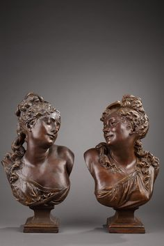 Two feminine busts in terra-cotta in the taste of Albert Ernest Carrier-Belleuse. The hair attached on the top of their head in bun, escape in wide waves on...
