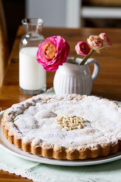 Aprende a realizar una sencillísima tarta rellena con una deliciosa crema pastelera y piñones. Receta paso a paso con fotografías.