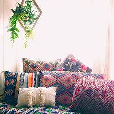 I want a blend of fun, vibrant colors like these pillows with clean, calming elements like the white walls and hanging plants.