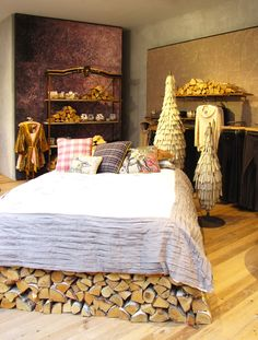 I love the idea of creating the effect of stacked wood holding up a bed (hiding the risers). From Anthropologie London, RegentStreet