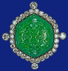 Emerald and diamond brooch - presented to Queen Mary at the Delhi Durbar by the Ladies of India and inherited by The Queen in 1953 - large hexagonal emerald, in a gold and silver setting encircled by brilliant-cut diamonds, is carved with a rose on the front and a plant on the back.