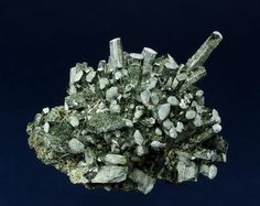 Hedenbergite- CaFe2+Si2O6, Huanggangliang Iron Mine, Kèshíkèténg Qí, Chifeng, Inner Mongolia A.R., China 89.0 x 65.0 x 49.0 mm Elongate, semi-lustrous, green tabular crystals of Hedenbergite are arranged in a semi-radiating structure, and are accented with white on the apical termination. Several clear and etched crystals of Calcite to 8 mm are perched on the Hedenbergite. A nice specimen from this prolific locality with no damage. (Author: GneissWare)