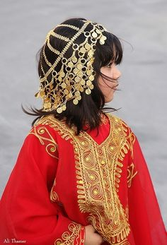 Girl from Bahrain - Stunning gold thread embroidery on the kaftan-style gown is echoed in the headdress
