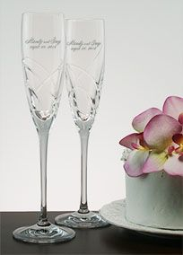 From the Lenox Adorn collection, these crystal toasting flutes will provide timeless beauty to your reception table.  Crafted of Lenox fine crystal, a distinctive deeply cut ribbon-like pattern graces the bottom half of the flute bowls.  Personalizing these flutes will add a custom touch to your reception and easily transform them in to treasured wedding keepsakes.  Choose from a variety of different font options and we will deeply sand blast it on to your flutes by ...