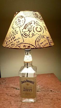 """Abajur cuja base é uma garrafa de whisky """"JACK DANIELS HONEY"""" Exclusividade de CARLLOS CRIAÇÕES..Segue com a cúpula, a parte elétrica completa, testada, pronto para ser utilizado (segue sem a lâmpada). <br>Preço PROMOCIONAL DE LANÇAMENTO! <br>Despachamos para todo o Brasil."""