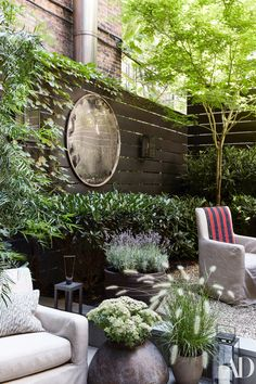 In the garden, designed by Harrison Green, custom armchairs by August Studios wear a Holly Hunt acrylic. Vintage highway mirror on wall.