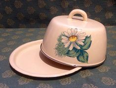 A vintage enamelware dish in cream with large Daisy and leaves on each side. This could be Russian and dates from the 1940s-1960s. Dish is 6 1/2 across and approx 4 tall, so could be used for a large block of butter, or for cheese. This does have two small areas of wear to the Enamel,
