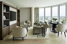 We made the most of the plentiful natural light with a softly neutral colour scheme whilst the bespoke media unit crafted in dark wood with brass trim created a striking focal point for the room. With some clever space-planning we were able to create separate zones for the living and dining areas in what was a relatively compact space. Study In London, Boutique Interior Design, Piano Room, Neutral Color Scheme, Floor To Ceiling Windows, Wood Plans, Open Plan Living, Pent House, Dining Area