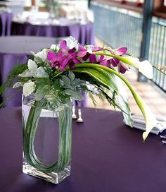 Modern Asian flower arrangement with white calla lilies, purple dendrobium orchids, dusty miller, tree fern and bear grass.