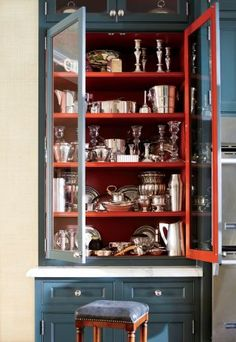Blue cabinets with red painted interiors - really highlights the silver being stored