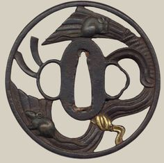 Tsuba.. Iron, inlaid with gold and copper . 18th century, Japan. The RöhsskaMuseum, of Design, Fashion and Decorative Arts , Sweden. The motif depicts two rats on a piece of fabric in high open-work relief with gold and copper inlays. A tsuba is a...