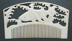 Edo ivory kushi with a carved relief of a whale swimming in the ocean.
